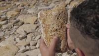 El hombre sostiene una piedra de mar en sus manos.