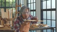 El artesano asiático sopla un poco de polvo de un palo de madera