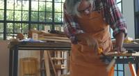 Asiatischer alter Zimmermann, der einen Holzstab sägt