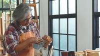 Asiatischer Handwerker, der Sandpapier verwendet, um ein Hausmodell zu schrubben
