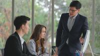 Gerente asiático explica o projeto para sua equipe