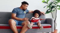 Der afrikanische Vater bringt seinem kleinen Sohn bei, zu Hause zu singen und Gitarre zu spielen
