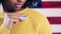 Ung väljare som sätter på jag röstade klistermärke efter valet