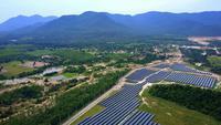 Drone vliegt hoog en recht over een zeer groot zonnepark op een zonnige dag.