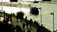 Silhouette de gens marchant près de la rivière