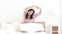 Mujer asiática joven que estira y que se relaja en cama