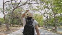 Vista posterior trasera de mujer con mochila caminando en parque público.