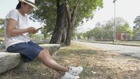 Aziatische vrouwenzitting onder de boom en het gebruiken van mobiele telefoon