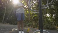 Femme asiatique avec sac à dos sur l'équipement d'exercice tout en utilisant le téléphone