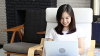 Asiatische junge Frau, die mit einem Laptop arbeitet
