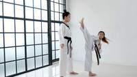 Wide shot van Taekwondo coach die haar student lesgeeft