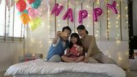 Vater und Mutter machen ein Foto mit Tochter in der Geburtstagsfeier.