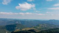 Vliegen over de wolken met bergen en heuvels