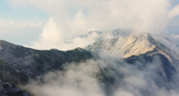 Drone Flying Over The Mountain Peaks With Fog