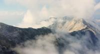 Drohne fliegt über die Berggipfel mit Nebel