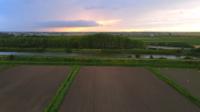 Gröna fält vid solnedgången med moln
