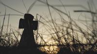 Silhouette d'une croix de pierre dans un champ