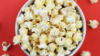 Popcorn vallen in een witte kom op een rode achtergrond