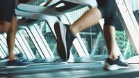 Hombres y mujeres atléticos corriendo ejercicio en cintas de correr
