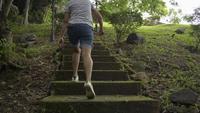 Vue arrière sur femme marchant sur l'ancien escalier en béton