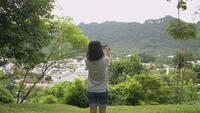 Vista trasera del turista caminando sobre el césped y tomando fotos desde la cima de la colina