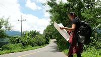 Mujer de mochilero con mapa por la carretera.