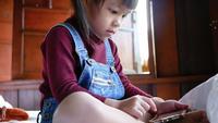 Junges Mädchen, das auf einem Smartphone spielt.