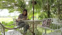 Frau, die auf einem Notizbuch im Freien schreibt