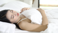 Mulher jovem asiática dormindo na cama