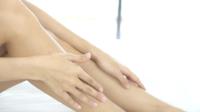 Mujer extendiendo crema hidratante en sus piernas