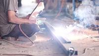 Cena em câmera lenta de soldador trabalhando com aço