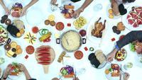 Vista superior de gente comiendo y bebiendo la cena en la mesa.