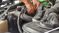 Mekaniker som kontrollerar kylfläkten på en bilmotor