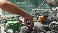Mekaniker som stänger oljelocket på bilmotorn