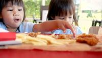 Niños comiendo comida frita en una tienda de comida rápida