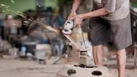 Trabajador artesano utiliza máquina pulidora de varillas de acero