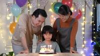 Asian Family Blowing Candles on A Birthday Cake at Home