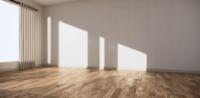 Een brede lege ruimte met houten vloer en witte muur
