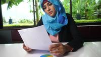 Young Arabic woman thoughtfully looking at paper chart