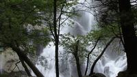 Uma cachoeira em cascata atrás das árvores