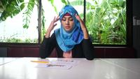 Woman wearing a hijab disappointed with results in business papers.