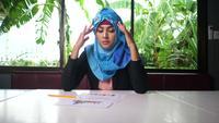 Vrouw die een hijab draagt, teleurgesteld over resultaten in handelspapieren.