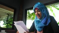 Woman wearing hijab excited with results in business papers.