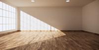 Un grand hall avec des murs blancs, du parquet et de grandes fenêtres