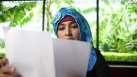 Junge arabische Geschäftsfrau, die Geschäftsbericht prüft