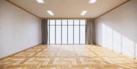 Una gran ventana en el centro de la habitación rodeada de paredes blancas y un piso de madera