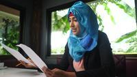 Junge arabische Frau, die zu Hause mit Geschäftskarte arbeitet