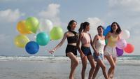 Grupo de chicas en la playa y sosteniendo globos