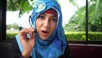 Young Arab woman working in a call center using a headset
