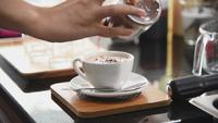 Barista streut eine Schokoladenflasche auf den Kaffee